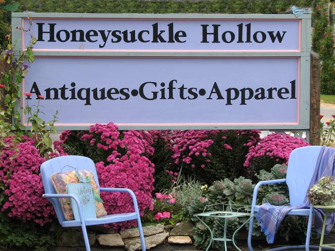 Sign and floral garden in front of store: Honeysuckle Hollow, Antiques, Gifts, Apparel